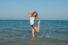 Junges Mädchen, welches das Wasser im Meer spritzt Lizenzfreie Stockfotos