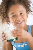 Junges Mädchen zuhause das Trinkmilchlächeln Lizenzfreie Stockbilder