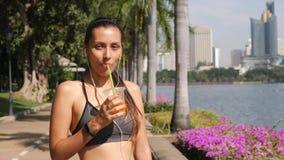 Junges Mischrasse-Läufer-Mädchen, das frischen Orangensaft trinkt und Kamera im Stadt-Park betrachtet 4k, Zeitlupe thailand stock footage
