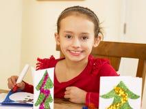 Junges Mischrennenkind, das Weihnachtskarten bildet Lizenzfreie Stockfotos