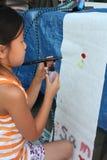 Junges mit der Spritzpistole bearbeitendes Mädchen Stockbilder
