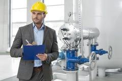 Junges männliches Aufsichtskraftschreiben auf Klemmbrett in der Industrie Stockfotos