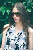 Junges Modefrauenporträt mit Sonnenbrille im Garten lizenzfreies stockfoto