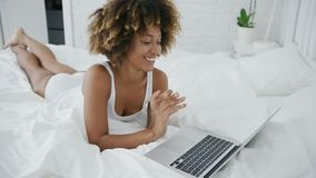Junges Modell mit Laptop im Bett stock footage
