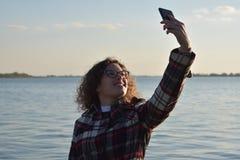 Junges modernes Herbstmädchen, das selfie durch den See macht Lizenzfreie Stockfotos