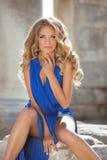 Junges modernes lächelndes Mädchenmodell, das im blauen Kleid aufwirft beaut Stockfotos