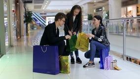 Junges modernes Mädchen mit den Eltern, die Käufe in den Einkaufstaschen betrachten stock video