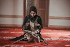 Junges moslemisches Mädchen, das eine Heilige Schrift liest stockfoto