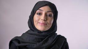 Junges moslemisches Mädchen im hijab öffnet Augen und Uhren an der Kamera und lächelt, religiöses Konzept, grauer Hintergrund