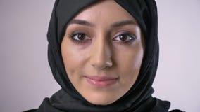 Junges moslemisches Mädchen im hijab öffnet Augen und Uhren an der Kamera und träumt Konzept, grauer Hintergrund