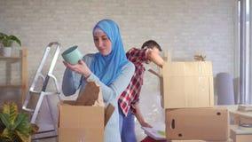 Junges moslemisches Paar baut Kästen auseinander, nachdem es sich bewegt hat stock video footage