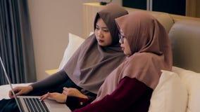 Junges moslemisches Uhrvideo der Frau zwei auf Laptop im Schlafzimmer stock video