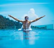 Junges, muskulöses Schwimmerspritzwasser stockfotografie
