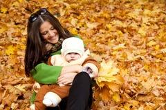Junges Mutterholdingschätzchen im Park Lizenzfreie Stockfotos