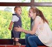 Junges Muttermädchen des Porträts und Babysohn glücklich zusammen zu Hause stockfoto