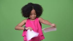 Junges nettes afrikanisches Mädchen mit dem Afrohaar, das Schreibarbeit zerreißt stock video