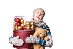 Junges nettes lächelndes Mädchen in der Strickjacke, einen Kasten Weihnachtsdekorationen halten Winter, Cristmastime, Neujahrsfei Stockbilder