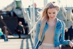 Junges nettes Mädchen auf der Küste Junges blondes Frauenlächeln Modische Art Lizenzfreies Stockfoto