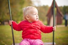 Junges nettes Mädchen, das auf Spielplatz im Park schwingt Stockfoto