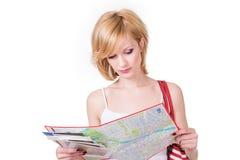 Junges nettes Mädchen, das Karte vor Reise betrachtet stockfotografie