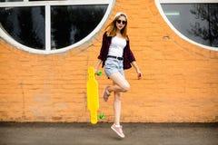 Junges nettes Mädchen, das mit gelbem Skateboard gegen orange Wand aufwirft stockfoto