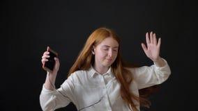 Junges nettes Mädchen mit dem Ingwerhaar in der hörenden Musik und in Tanzen des weißen Hemdes, lokalisiert auf schwarzem Hinterg stock video