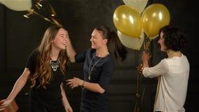 Junges nettes Mädchen mit dem langen Haar-Umarmen Freunde für das Geben ihr eines Geschenkes Zwei lächelnde Frauen, die Bündel Ba stock footage