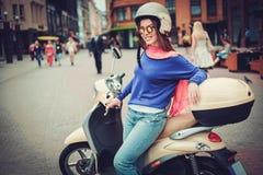 Junges nettes Mädchen nahe Roller herein in der europäischen Stadt Stockfoto