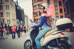 Junges nettes Mädchen nahe Roller herein in der europäischen Stadt Lizenzfreie Stockfotografie