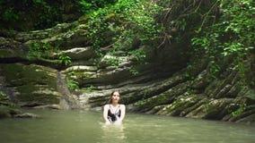 Junges nettes Mädchen spritzt auf Wasser durch Hände im kleinen Gebirgssee nahe Wasserfall im grünen tropischen Wald stock footage
