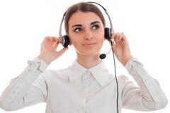 Junges nettes Mädchenhändchenhalten, das Kopfhörer auf ihrem Kopf und Blicken in Richtung zu lokalisiert auf weißem Hintergrund t Stockbilder