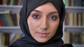 Junges nettes moslemisches Mädchen im hijab passt an der Kamera auf und passt unten in Buch, religiöses Konzept, Bücherregal auf