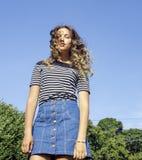 Junges nettes Sommermädchen auf grünem Gras draußen Stockfotografie
