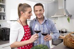 Junges neues verheiratetes Paar in der Küche zusammen kochend Stockbilder