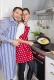 Junges neues verheiratetes Paar in der Küche kochend zusammen gebraten Lizenzfreie Stockfotografie
