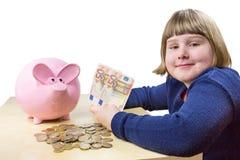 Junges niederländisches Mädchen, das Eurogeld und Sparschwein zeigt Lizenzfreie Stockfotografie