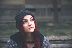 Junges obdachloses Mädchen, das auf der Straße auf der Bank sitzt stockfotos