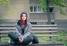 Junges obdachloses M?dchen, das auf der Stra?e auf der Bank sitzt lizenzfreies stockfoto