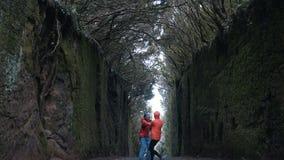 Junges optimistisches Paarhändchenhalten geht und dreht sich herum auf eine Tunnelstraße zwischen die Felsen, die durch Bäume in  stock video