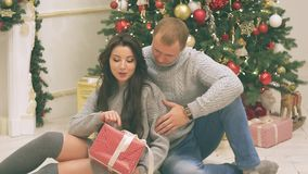 Junges Paar in der Liebe im Dekor des neuen Jahres mit Geschenken und Weihnachtsbaum, dort ist Geräusche im Video stock video