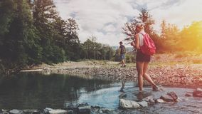 Junges Paar geht entlang die Bank von einem Gebirgsfluss im Sommer Ein Mädchen mit einem Rotluchs kreuzt den Fluss für eine Furt, stockfotografie