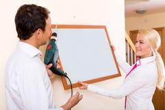 Junges Paar hängt ein Bild Lizenzfreie Stockbilder