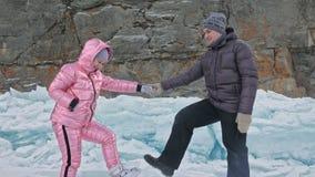 Junges Paar hat Spaß während des Winterwegs gegen Hintergrund des Eises von gefrorenem See Liebhaber gehen auf Eis, sich halten v stock video footage