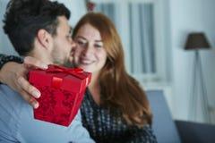 Junges Paar ist mit Geschenk für Weihnachten glücklich lizenzfreie stockbilder