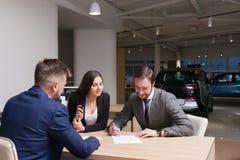Junges Paar legt an kaufenden und unterzeichnenden Papieren fest Lizenzfreie Stockbilder