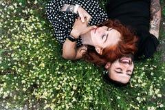 Junges Paar liegt auf dem Feld mit Gänseblümchen lizenzfreie stockfotos