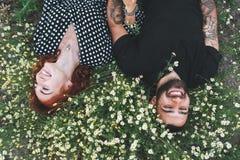 Junges Paar liegt auf dem Feld mit Gänseblümchen lizenzfreies stockfoto