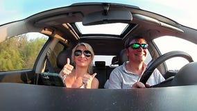 Junges Paar reitet ein Auto an einem sonnigen Tag stock footage