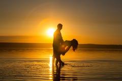 Junges Paar tanzt in das Wasser auf Sommerstrand Sonnenuntergang ?ber dem Meer Zwei Schattenbilder gegen die Sonne Ruhig und noch stockfotografie