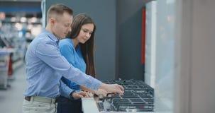 Junges Paar w?hlt cooktop im Speicher von Haushaltsger?ten stock video